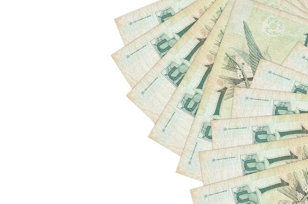 1ブラジルレアルの請求書は、コピースペースのある白い壁に隔離されています。大量の自国通貨資産