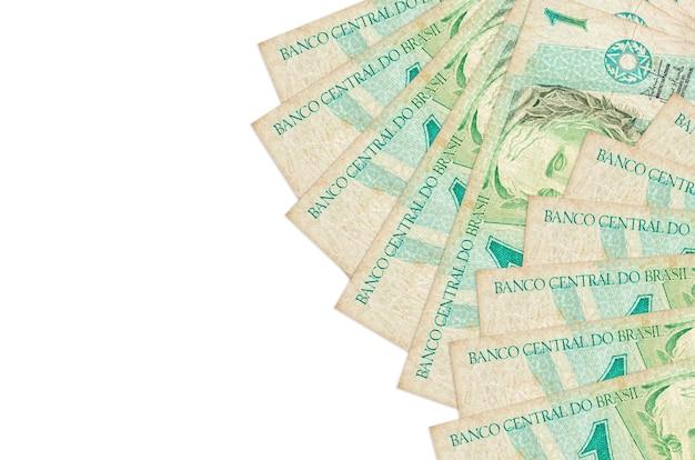 1ブラジルレアルの請求書は、コピースペースのある白い壁に隔離されています。豊かな生活の概念的な壁。大量の自国通貨資産