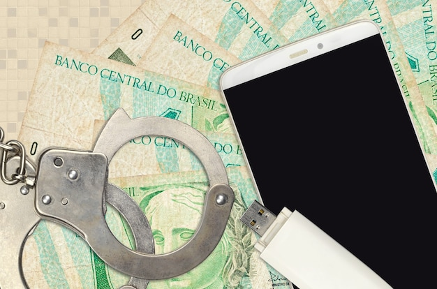 1 brazilian real bills and smartphone with police handcuffs