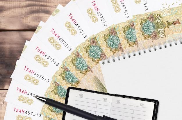 1人民元の請求書ファンと連絡帳と黒のペン付きのメモ帳。フィナンシャルプランニングとビジネス戦略の概念。会計と投資