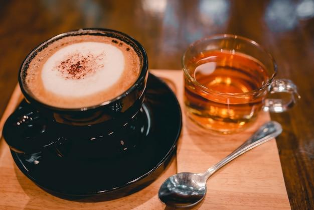 Горячий кофе в черной чашке и 1 чашке чая, который подается вместе в кафе во время вируса короны или covid-19