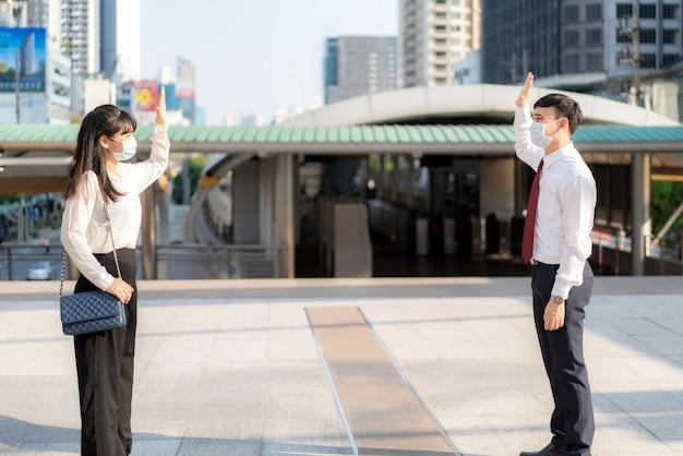 アジアのビジネスの男性と女性が挨拶し、ビジネスの同僚と挨拶をし、1メートルの距離の立ちマスクを着用してcovid-19ウイルスから保護する
