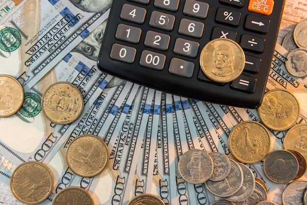 1 ドル紙幣の背景に横になっている電卓でコイン