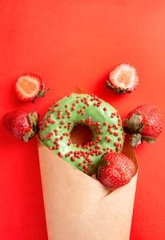 녹색 유약과 빨간 뿌리를 가진 도넛 1 개, 빨간 표면에 봉투에있는 신선한 딸기