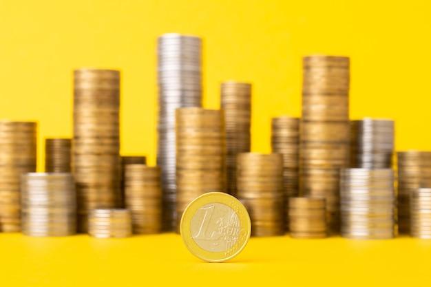 동전 더미와 노란색 테이블에 1 유로 동전