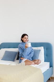 彼女の手で熱いお茶を1杯とインテリアhyggeスタイルの青いセーターの女の子がベッドに座っています。