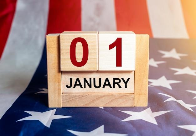 アメリカの国旗を背景に木製のカレンダーで1月1日。新年とルールの概念。