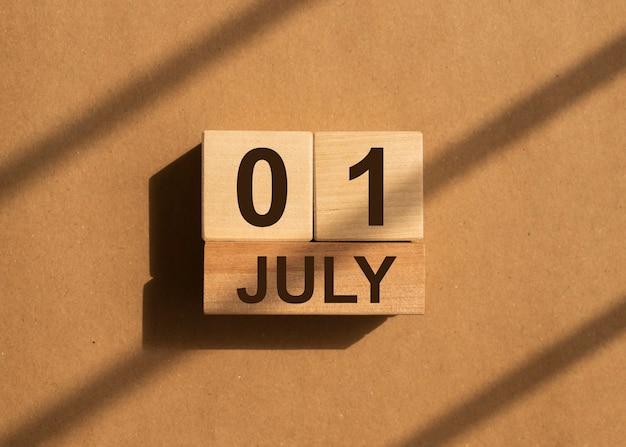 日光の茶色の紙の上に木製のカレンダーで7月1日。新しい月、1日目。