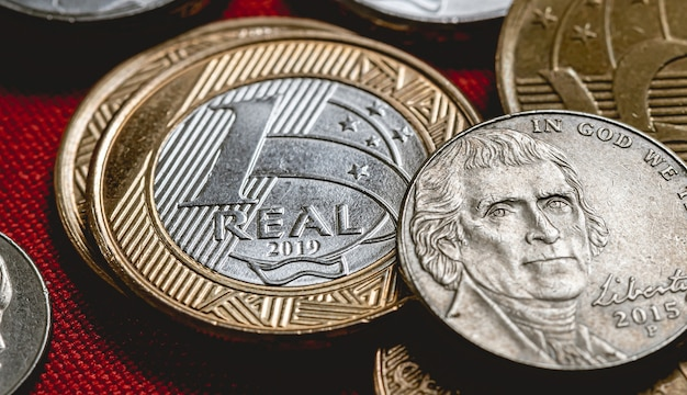 1 real brazilian coin with us dollar coins in close up photograph
