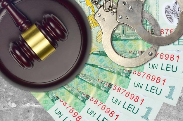 Банкноты в 1 румынский лей и молоток судьи с полицейскими наручниками на столе суда. понятие судебного разбирательства или взяточничества. уклонение от уплаты налогов или уклонение от уплаты налогов
