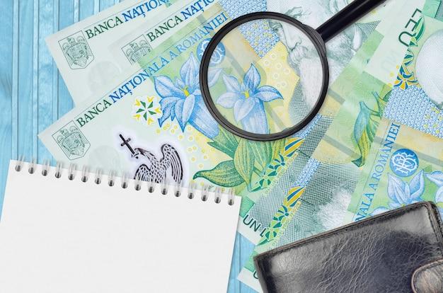 Банкноты 1 румынский лей и увеличительное стекло с черным кошельком и блокнотом