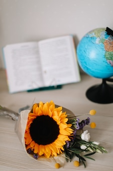 1 september back to school concept bouquet with sunflower and school supplies on table