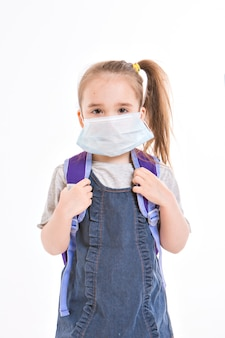 1 september. first-grader in medical school is going to school. little girl on home distance learning. child with school backpack works. the student is doing homework. isolated on a white background
