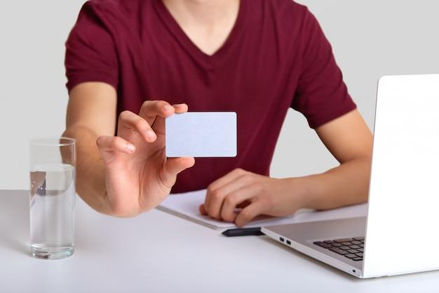 ラップトップコンピューター、コップ1杯の水で職場に座っているカジュアルな赤いtシャツで認識できない男をトリミング、広告コンテンツやプロモーション用の空き容量のある空白のカードに焦点を当てる