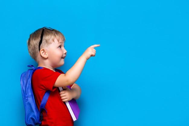 学校に戻る1年生のジュニアライフスタイル。赤いtシャツの小さな男の子。カバンと彼の指で指している本とメガネで微笑む少年のスタジオ写真の肖像画を間近します。