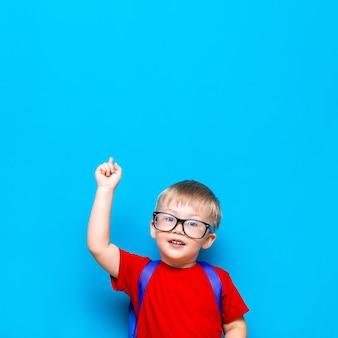 学校に戻る1年生のジュニアライフスタイル。赤いtシャツの小さな男の子。彼の指で上向き、通学かばんでメガネで微笑む少年のスタジオ写真の肖像画を間近します。