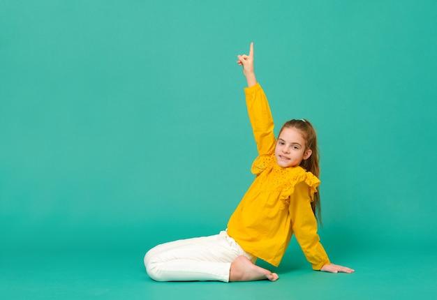 노란색 블라우스를 입은 10 세 소녀 1 명은 바닥에 앉아 녹색 표면에 손을 보여줍니다.