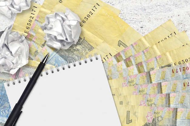 1 ukrainian hryvnia bills and balls of crumpled paper with blank notepad. bad ideas or less of inspiration concept. searching ideas for investment
