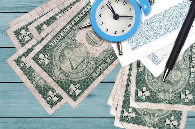 1 us dollar bills and alarm clock with pen and envelopes