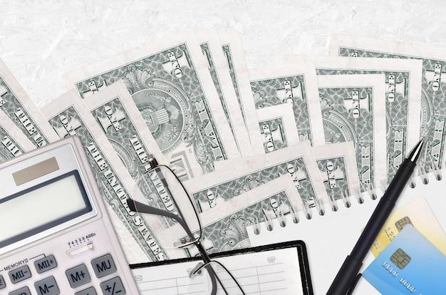 Банкноты 1 доллар сша и калькулятор с очками и ручкой. концепция уплаты налогов или инвестиционные решения. финансовое планирование или бухгалтерские документы