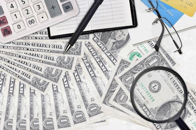 Купюры 1 доллар сша и калькулятор с очками и ручкой. концепция сезона уплаты налогов или инвестиционные решения. ищу работу с высоким заработком