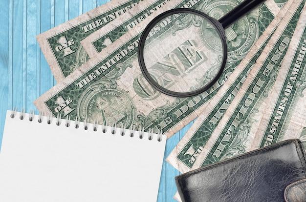 Банкноты 1 доллар сша и увеличительное стекло с черным кошельком и блокнотом