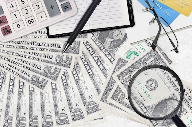 1 us dollar bills and calculator with glasses and pen. tax payment season concept or investment solutions. searching a job with high salary earnings