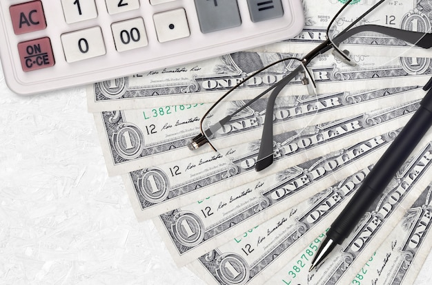Вентилятор банкнот 1 доллар сша и калькулятор с очками и ручкой. бизнес-кредит или концепция сезона налоговых платежей.