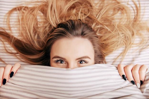 1 белая блондинка в постели, выглядывающая из-под одеяла и улыбающаяся