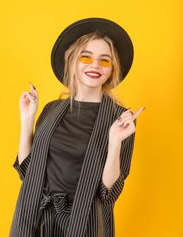 黒のスーツ、帽子、眼鏡の1人の白人の若い生意気なブロンドの女性が黄色の表面に微笑む