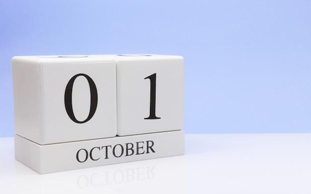 10月1日月の1日目、白いテーブルに毎日のカレンダー