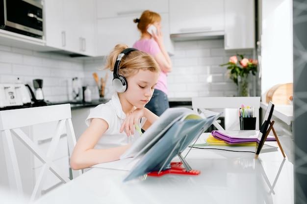 10代の女子高生が、自宅から離れた家庭教師とオンライン学習会議通話ヘッドセットを着用しています。お母さんが電話で話している、10代の学生がラップトップを使用している、ウェブカメラでビデオチャットを話している、lを教えている
