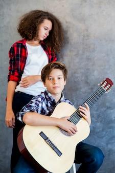 10代の少女が彼を聞いている間アコースティックギターを弾く10代の少年