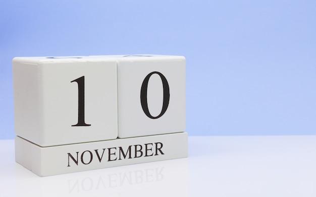 10 ноября день 10 месяца, ежедневный календарь на белом столе с отражением, с голубым фоном.