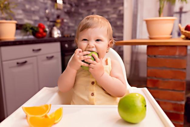 幸せな赤ちゃん10〜12ヶ月は果物を食べる:オレンジ、リンゴ。キッチンのハイチェアで幸せな少女の肖像画
