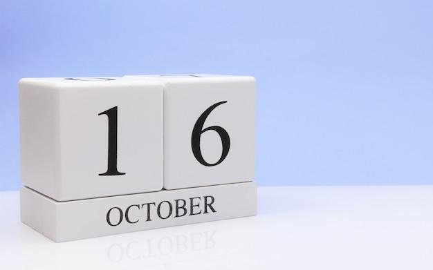 10月16日月16日、白いテーブルに毎日のカレンダー
