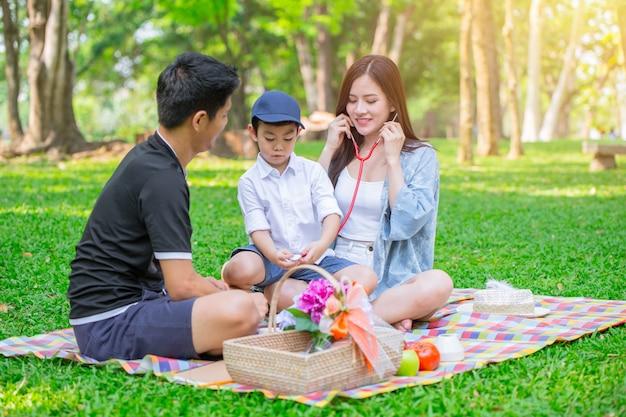 アジアの10代の家族1人の子供の幸せな休日のピクニックの瞬間は、公園で医師としての役割を果たします。