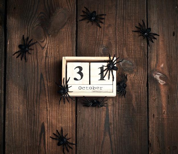 10月31日の日付のブロックで作られた黒いクモの置物と木製のレトロな時計