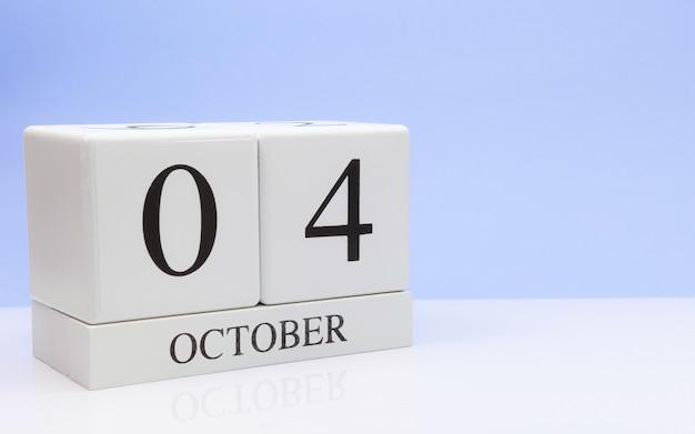 10月4日月の4日目、白いテーブルに毎日のカレンダー