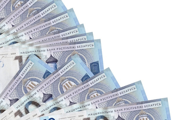 Купюры 10 белорусских рублей лежат изолированно на белой стене с копией пространства, сложенными в веер крупным планом. понятие времени выплаты жалованья или финансовые операции