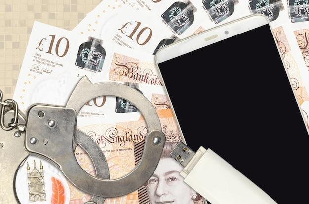 10英国ポンド紙幣と警察の手錠付きスマートフォン