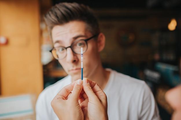 妊娠テストを保持している10代のccoupleを驚かせた。女性は、男性の肯定的な妊娠検査の対立関係の問題、悲しい否定的な感情を示しています。