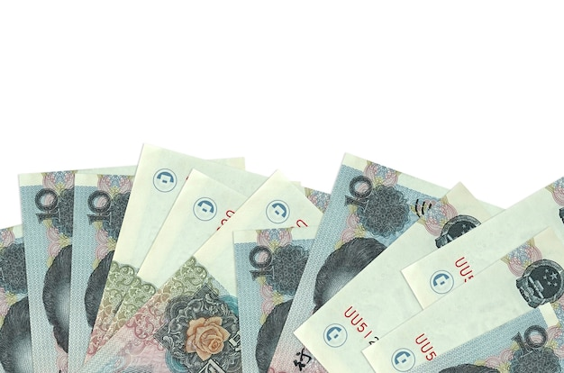 10 chinese yuan bills lies on bottom side of screen isolated on white wall with copy space.