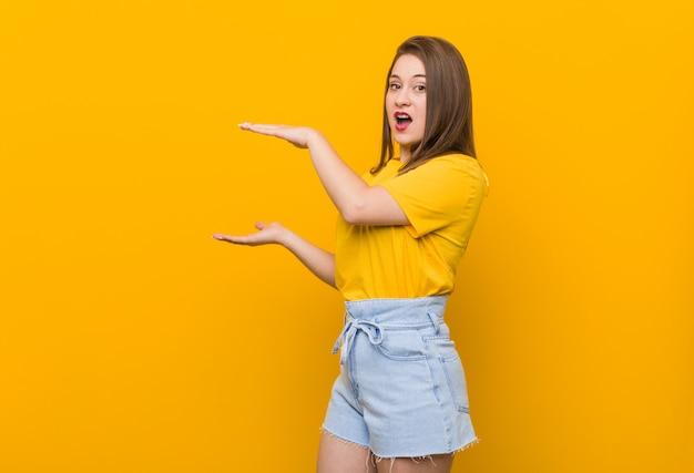 黄色のシャツを着た若い女性10代は、手の間copyspaceを保持してショックを受け、驚いた。