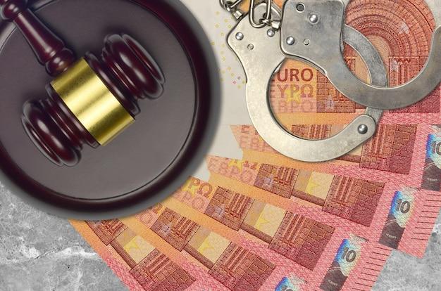 10ユーロ紙幣と裁判所の警察の手錠でハンマーを判断する