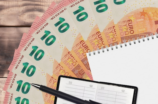 10 euro bills fan and notepad with contact book and black pen. concept of financial planning and business strategy. accounting and investment