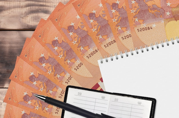 10 euro bills fan and notepad with contact book and black pen. concept of financial planning and business strategy
