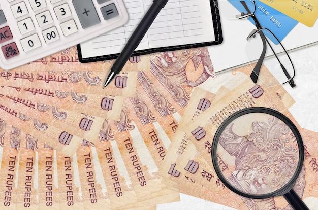 Банкноты 10 индийских рупий и калькулятор с очками и ручкой. концепция сезона уплаты налогов или инвестиционные решения. ищу работу с высоким заработком