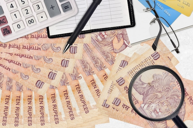 10 indian rupees bills and calculator with glasses and pen. tax payment season concept or investment solutions. searching a job with high salary earnings