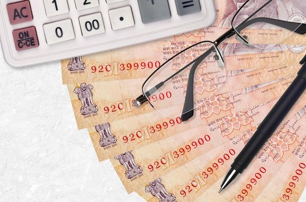 Вентилятор банкнот 10 индийских рупий и калькулятор с очками и ручкой